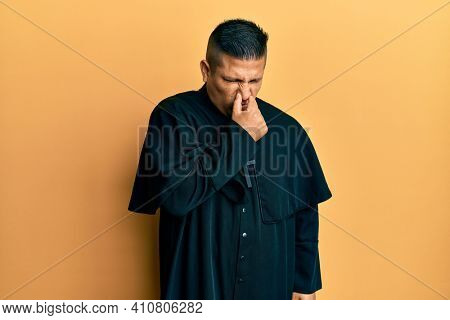 Young latin priest man standing over yellow background smelling something stinky and disgusting, intolerable smell, holding breath with fingers on nose. bad smell
