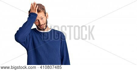 Handsome blond man with beard wearing casual sweater surprised with hand on head for mistake, remember error. forgot, bad memory concept.