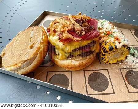 Fast Food Hamburger With Truffle Sauce And Served With Corn And Parmesan Cheese In Tray At Burger Re