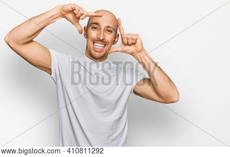 Bald man with beard wearing casual white t shirt smiling making frame with hands and fingers with happy face. creativity and photography concept.