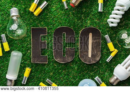 Used Metal Lithium Alkaline Batteries And Lightbulbs On Grass Background