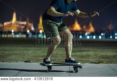 Asian Cheerful Man Playing Surfskate Or Skate Board In Outdoor Park At Night Over Photo Blur Of Bang
