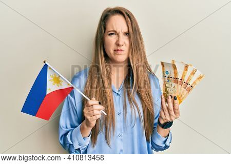 Young blonde woman holding philippine flag and philippines pesos banknotes skeptic and nervous, frowning upset because of problem. negative person.