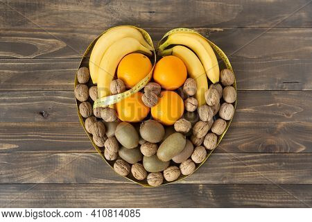 Top View Of Assorted Fruit And Dried Fruits Forming A Heart On A Dark Wood Background. Healthy Eatin