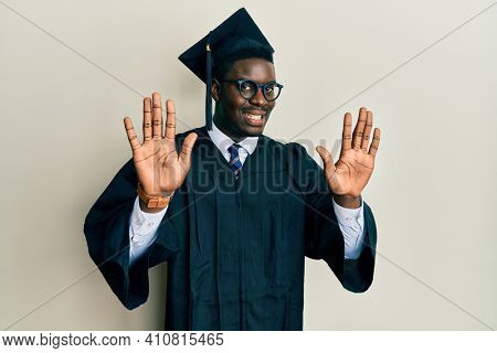 Handsome black man wearing graduation cap and ceremony robe showing and pointing up with fingers number ten while smiling confident and happy.