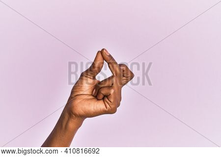 Arm and hand of black middle age woman over pink isolated background snapping fingers for success, easy and click symbol gesture with hand