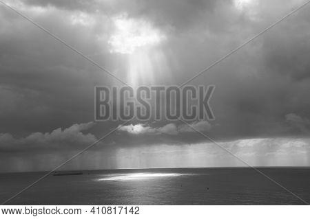 Light Peeping Through A Breach In Grey Storm Clouds