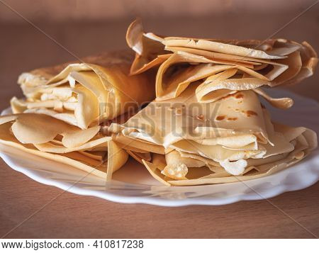 Pancakes Smeared With Butter And Rolled Up Envelopes Lie On A White Plate Close-up