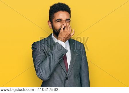 Young african american man wearing business clothes smelling something stinky and disgusting, intolerable smell, holding breath with fingers on nose. bad smell