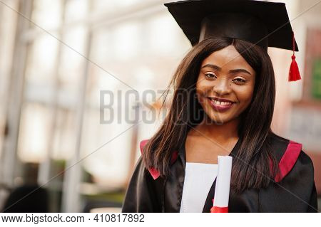 Young Female African American Student With Diploma Poses Outdoors.