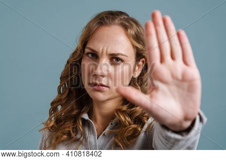 Displeased beautiful blonde girl showing stop gesture at camera isolated over blue background