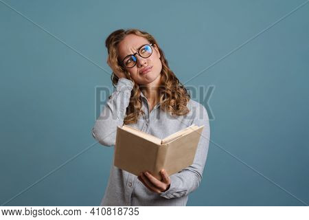Displeased beautiful girl in eyeglasses reading book isolated over blue background