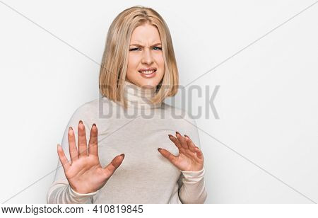 Young blonde woman wearing casual clothes disgusted expression, displeased and fearful doing disgust face because aversion reaction. with hands raised