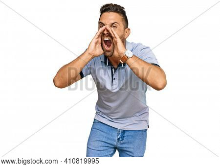 Handsome man with beard wearing casual clothes shouting angry out loud with hands over mouth