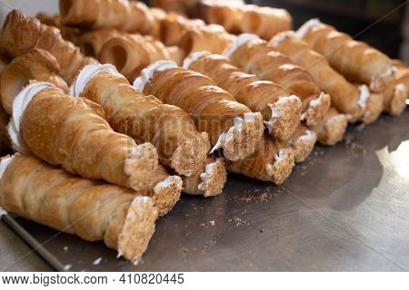 On A Metal Board Lie Puff Pastry Rolls With Protein And Custard, Sprinkled With Powdered Sugar. Puff