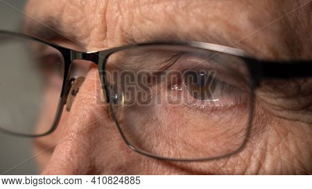 Close-up View Of A Focused Mature Man Wearing Computer Glasses To Reduce Eye Strain, Reading The Int