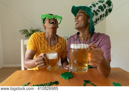 Laughing mixed race gay male couple wearing st patrick's day costumes and raising glasses of beer. staying at home in isolation during quarantine lockdown.