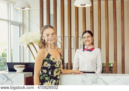 Happy Guest And Receptionist At Hotel Reception, Young Travellers Standing At Reception Desk With Bl
