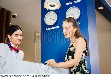 Happy Guest And Receptionist At Hotel Reception, Young Travellers Standing At Reception Desk With Fe