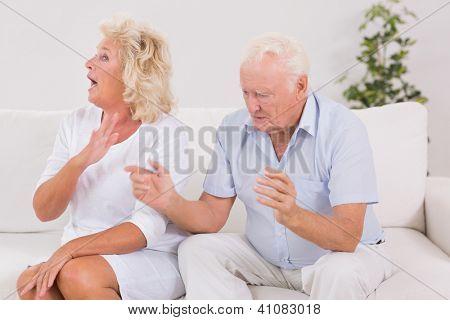 Elderly couple quarrelling on the sofa