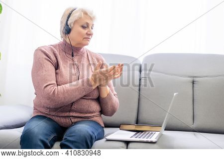 Elderly Woman Stay At Home Wearing Headphone Pray And Worship God With Laptop. Prayer Elderly Woman