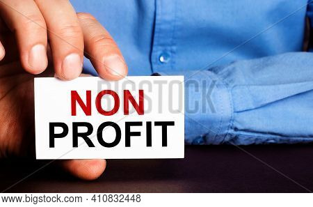 Non Profit Is Written On A White Business Card In A Man's Hand. Advertising Concept