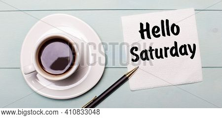 On A Light Blue Wooden Tray, There Is A White Cup Of Coffee, A Handle And A Napkin That Says Hello S