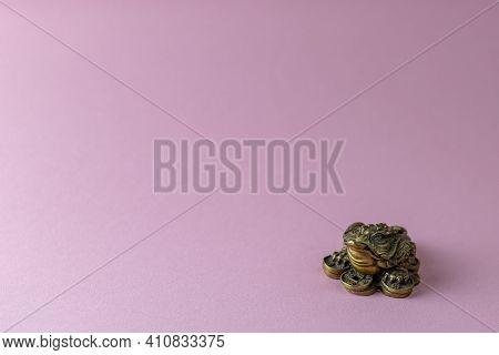Feng Shui Money Mascot - Chang Chu - Bronze Figure Of A Frog Sitting On Coins, Isolated On A Pink Ba