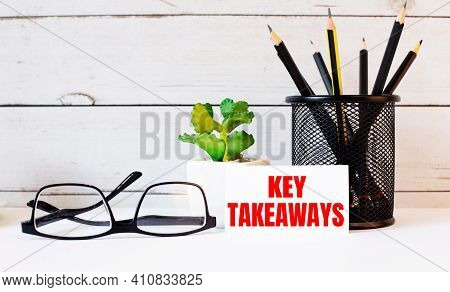 The Words Key Takeaways Written On A White Business Card Next To Pencils In A Stand And Glasses. Nea