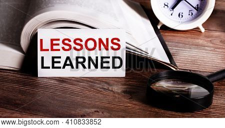 The Words Lesson Learned Written On A White Card Near An Open Book, Alarm Clock And Magnifying Glass