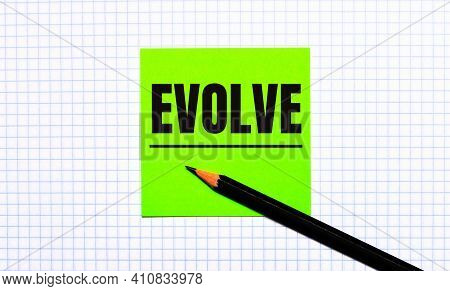 There Is A Green Sticker With The Text Evolve And A Black Pencil On The Checkered Paper.