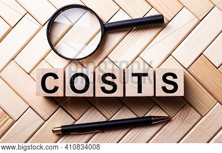Wooden Cubes With The Word Costs Stand On A Wooden Background Between A Magnifying Glass And A Pen