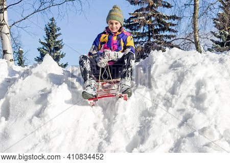 Happy Smiling Girl Ride Downhill On Children`s Sleds. Winter Outdoor Fun.