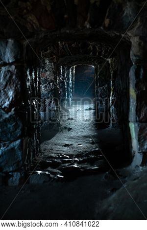 A Dark, Damp, Cold Dungeon Corridor With Stone Walls All Along The Hallway