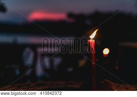 A Single Red Candle Burns In The Tropical Sunset Of Cambodia