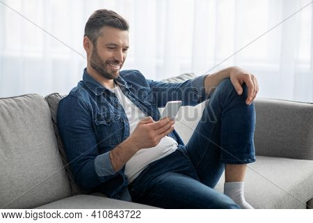Happy Middle-aged Man In Casual Sitting On Couch At Home, Using Mobile Phone, Copy Space. Handsome B