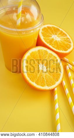 Orange Juice In Fast Food Closed Cup With Tube On Yellow Background. Sliced Orange And Yellow Paper