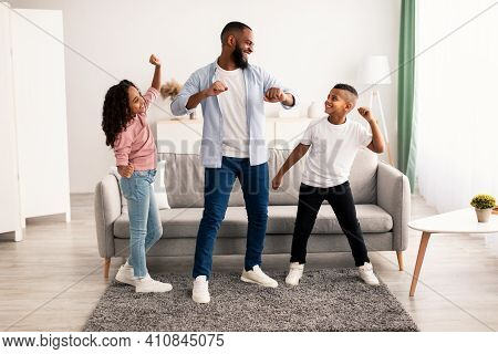 Spending Time Together Concept. Cheerful Black Dad Moving And Dancing To Music With His Excited Daug
