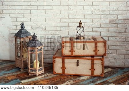 Decorative Vintage Suitcases And Lamps Against The Background Of A Textured Wall, A Stylized Photo Z