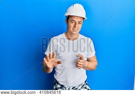 Handsome young man wearing builder uniform and hardhat disgusted expression, displeased and fearful doing disgust face because aversion reaction. with hands raised