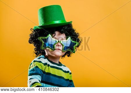 Patricks Day. Kid In Star Glasses And Green Top Hat Isolated On Yellow. Green Leprechaun. Saint Patr