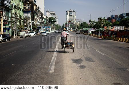 Yangon, Myanmar - January 1 2020: A Local Burmese Man In Traditional Longyi Rides His Bicycle Down T