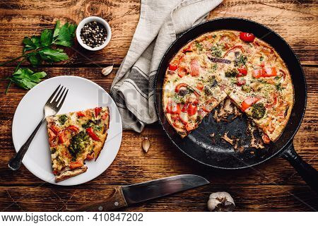 Vegetable Frittata With Broccoli, Red Bell Pepper And Red Onion On White Plate And In A Cast Iron. V