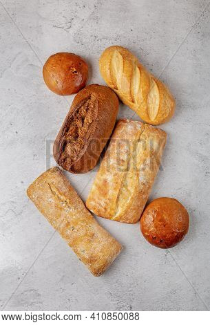 Baking Background With Several Different Fresh Baked Whole Loaves Of Bread Top View On Gray Surface