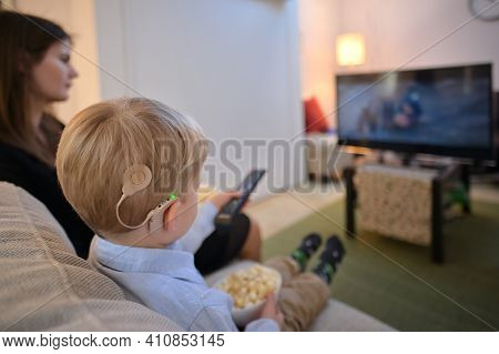 A Boy With Cochlear Implants Watching Television At Home
