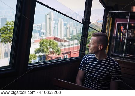 Young Man Travelling By Tram To Victoria Peak And Looking Through Window While Visiting Hong Kong.