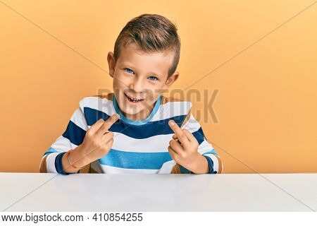 Adorable caucasian kid wearing casual clothes sitting on the table showing middle finger doing fuck you bad expression, provocation and rude attitude. screaming excited