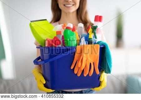 Unrecognizable Millennial Maid Holding Bucket With Cleaning Supplies Indoors, Closeup Of Hands. Crop