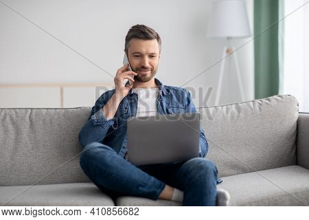 Positive Middle-aged Bearded Man With Laptop Talking On Smartphone, Sitting On Sofa In Living Room,
