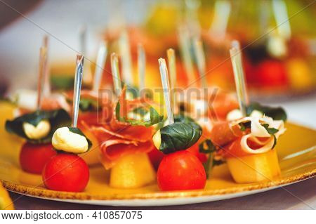 Buffet At The Reception. Glasses Of Wine And Champagne. Assortment Of Canapes On A Wooden Board. Ban